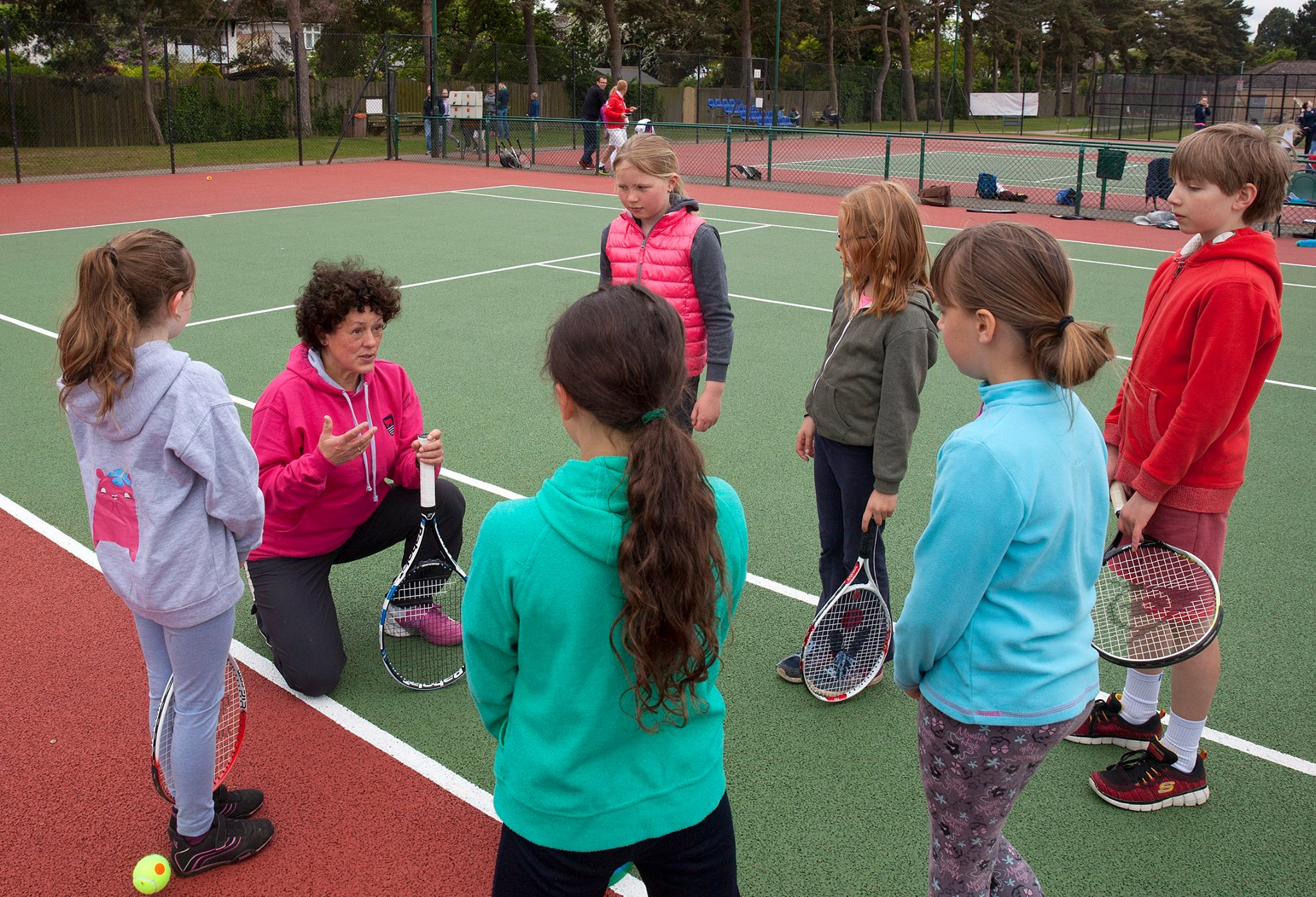 Coach Maddie on-court witha group of under-10 year old tennis players.